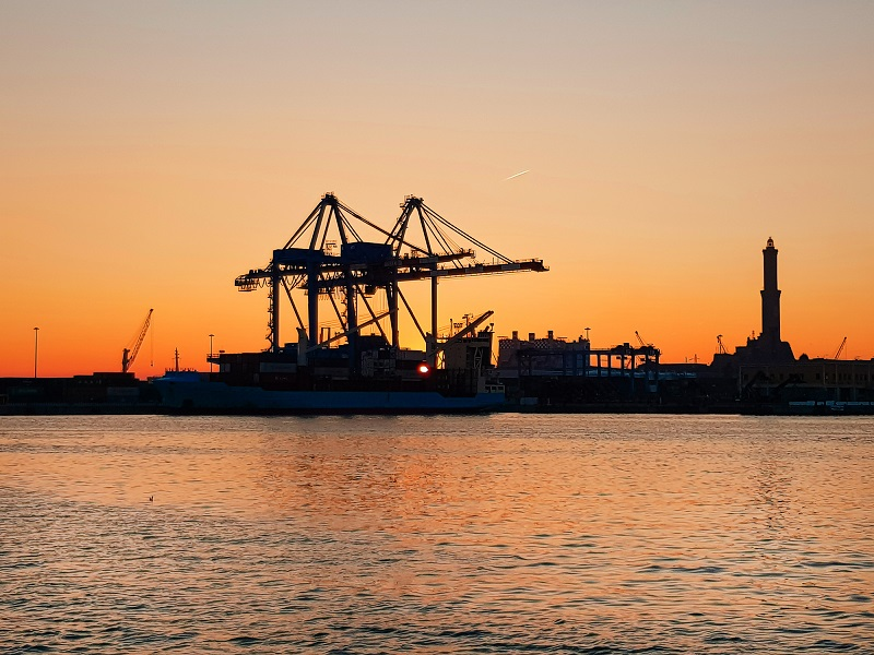 Industrial port at the Port of genoa italy with sunset, Containers loading Shipping by crane at sunset or Trade Port with silhouette background.
